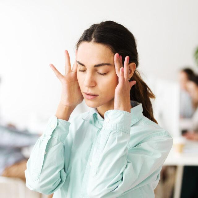kvinna med huvudvärk i grön skjorta